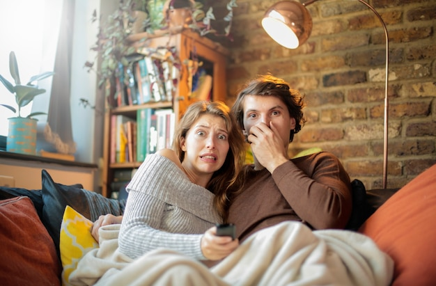 Friends looking a horror movie at home - couple watching tv, sitting on the sofa, cuddling under the blanket
