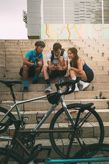 Friends looking at mobile phone sitting on stairs in sportswear near bicycle copy space vertical
