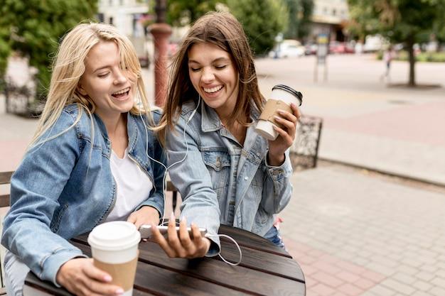 Друзья смотрят на телефон снаружи