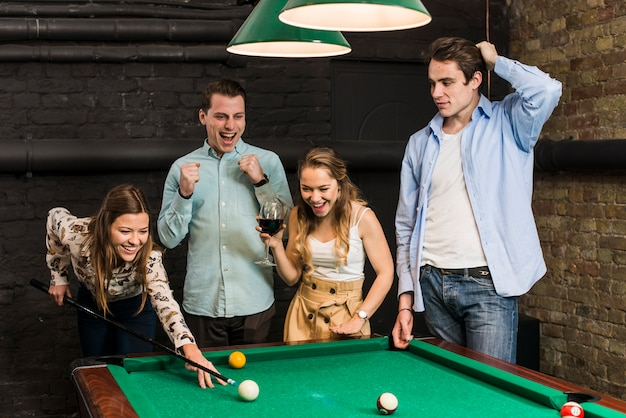 Friends looking at smiling woman playing snooker in club