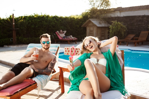 Friends lying on chaises near swimming pool, making selfie, smiling