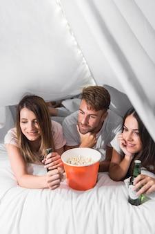 팝콘과 함께 침대에 누워있는 친구와 텔레비전을보고 음료