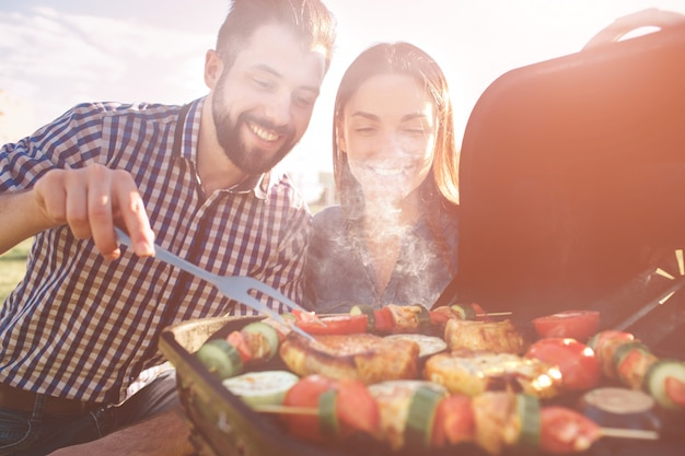Друзья готовят шашлыки и обедают на природе. пара весело во время еды и питья на пикник - счастливые люди на вечеринке барбекю.