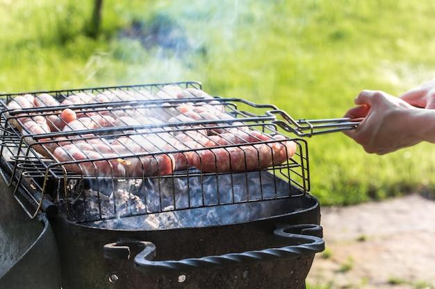 Друзья делают барбекю и обедают на природе.