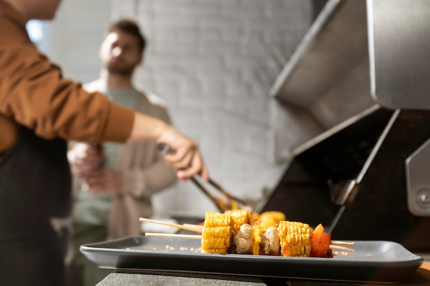 Friends making barbecue close up