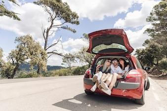 Friends making enjoyment in the car trunk on road