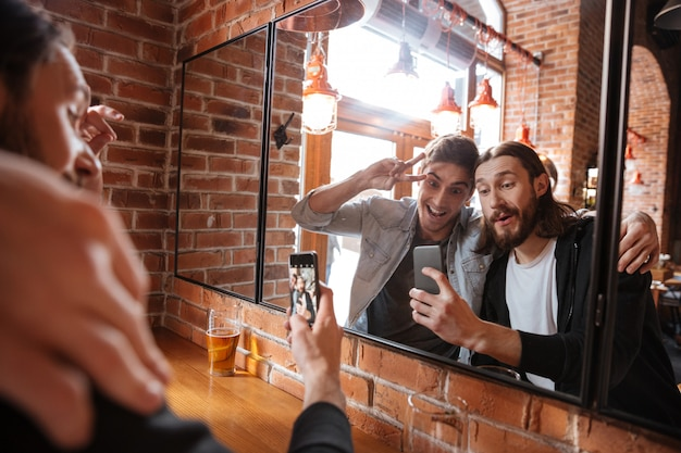 Друзья делают фото возле зеркала в баре