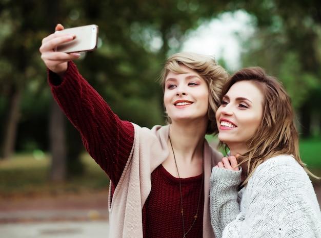Друзья делают селфи. две красивые молодые женщины, делающие селфи в осеннем парке.