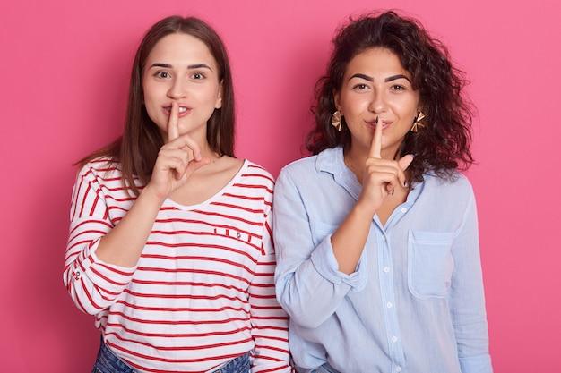 Друзья, делающие жест молчания, изолированные на розовой стене, брюнетки с пальцами у губ, в повседневных рубашках