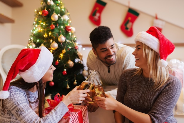 Friends making a toast while sitting in bedroom. christmas holidays concept.