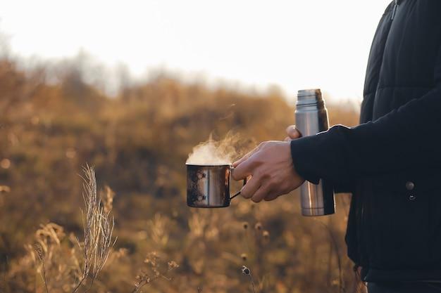 友達がコーヒーを飲みに会った秋の魔法瓶とスチーム寒い天気ホットコーヒーを手にホットティー