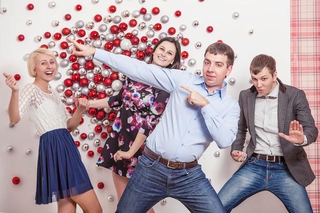 4人の男性と女性の友達がクリスマススタイルで楽しんで踊ったり笑ったりしています