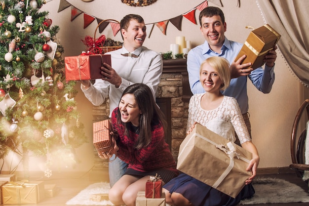 4人の男性と女性の友人がクリスマスのインテリアの木の下で贈り物をします