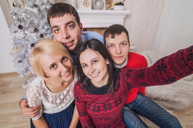 4人の男性と女性の友人がクリスマススタイルでモバイルで自画像を作成します