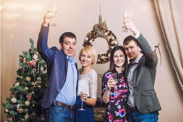 クリスマスのインテリアでシャンパンで祝うバケールの4人の男性と女性の友人