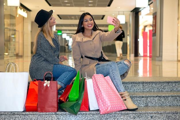買い物の日の友達は階段に座って自分撮りをして楽しんでいます