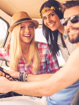 Друзья в поездке. трое веселых молодых людей смотрят в камеру и улыбаются, сидя в своем минивэне