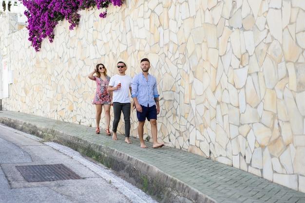 休暇中の友人が小さなヨーロッパの街の通りを歩く
