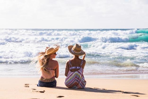 海と夏休みを楽しんでいるビーチで砂の上に座っている女の子の若いカップルと屋外の人々の友人