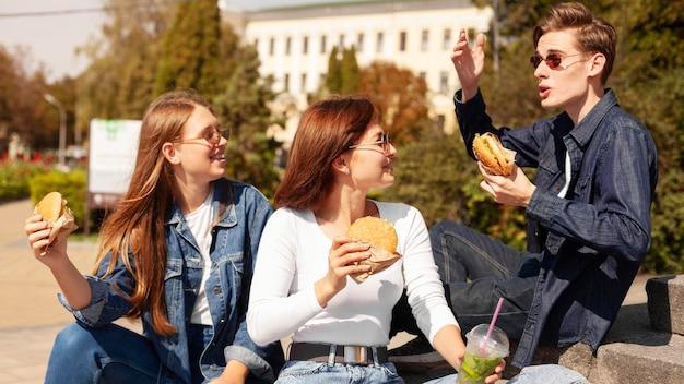 屋外でハンバーガーを食べる友達