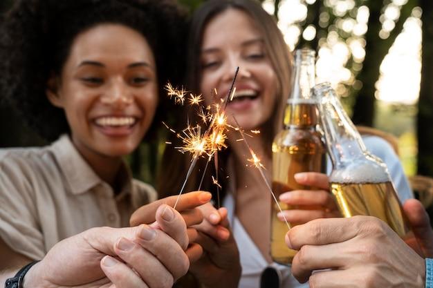 Amici all'aperto nel parco che bevono birra e si divertono con le stelle filanti