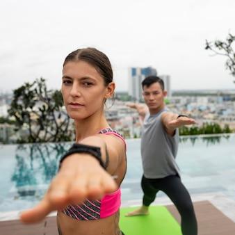 Друзья на открытом воздухе практикуют позы йоги у бассейна
