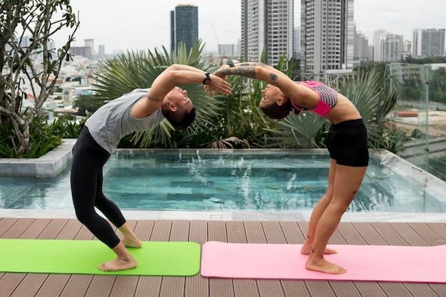 Друзья на открытом воздухе вместе занимаются позами йоги у бассейна