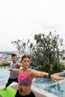 Друзья на открытом воздухе практикуют позы йоги