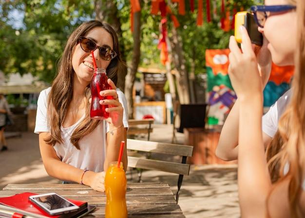Amici nel parco che tengono le bottiglie di succo fresco e scattare foto
