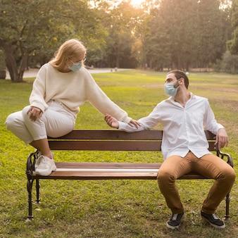 Amici al parco che praticano la distanza sociale