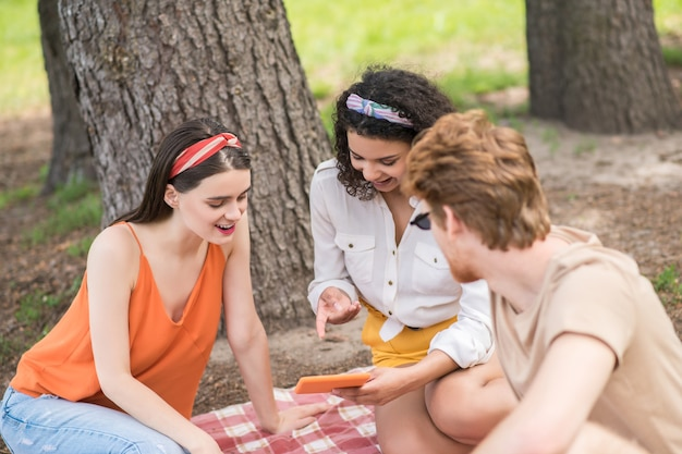 Friends, pastime. two young long-haired girls and red-haired guy looking into tablet communicating cheerful at picnic in park