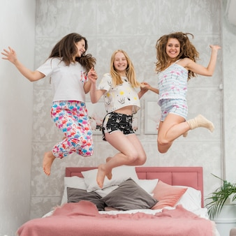Friends in pijama party jumping on the bed