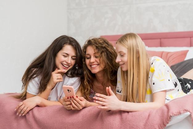 Gli amici in pigiama party guardando cellulare