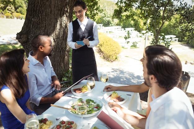 Друзья делают заказ официанту