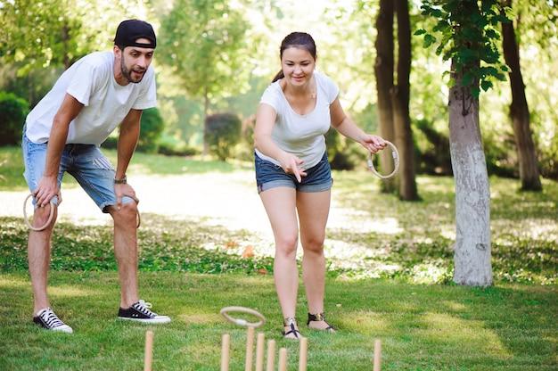 친구 plaing 야외 게임-여름 공원에서 링 던지기.