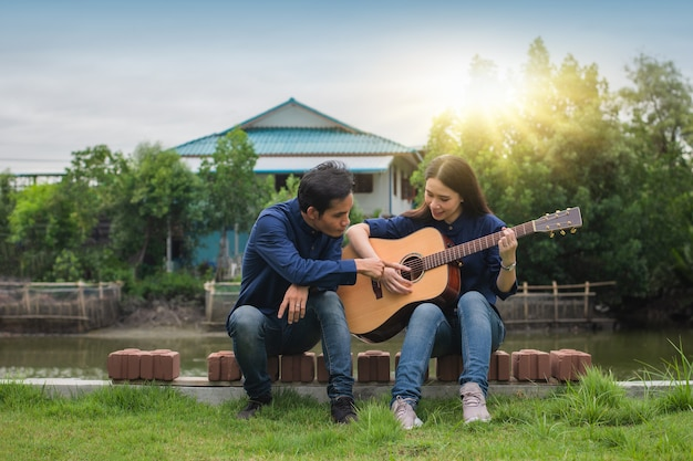 Friends play guitar together outdoors rest in summer holiday