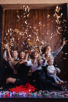 Friends play with confetti on new year celebration, home atmosphere, christmas