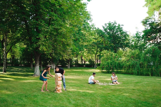 Друзья играют в настольную игру и домино на открытом воздухе.