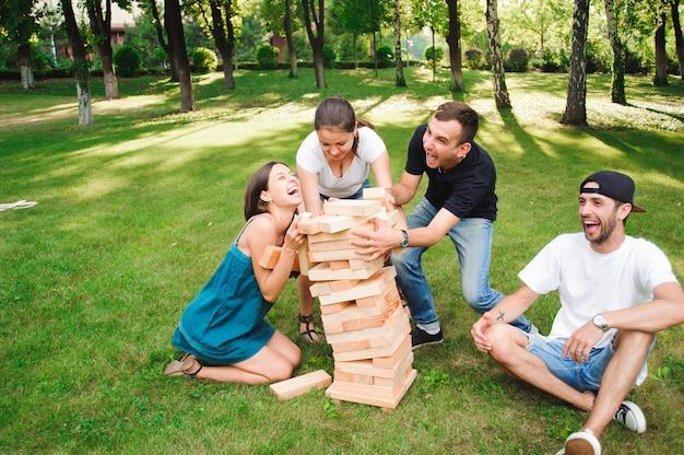 Друзья играют в настольную игру на открытом воздухе в парке.