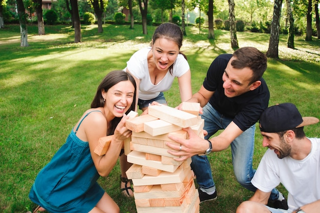 Friends playing board game outdoors in the park.