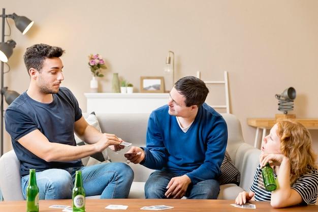 Amici a giocare a carte a casa e a bere birra