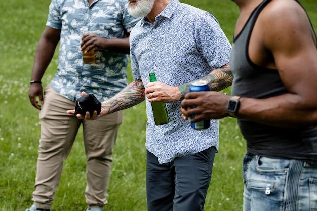 公園の夏のパーティーでコーンホールを遊んでいる友達