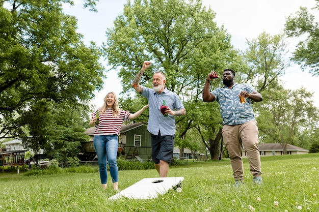 Amici che giocano a cornhole a una festa estiva nel parco