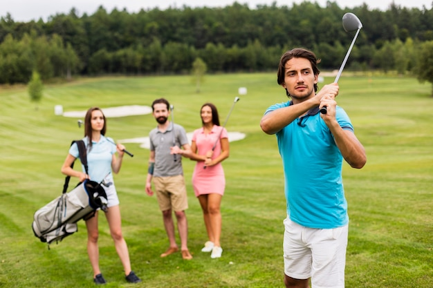 Friends playing golf on field