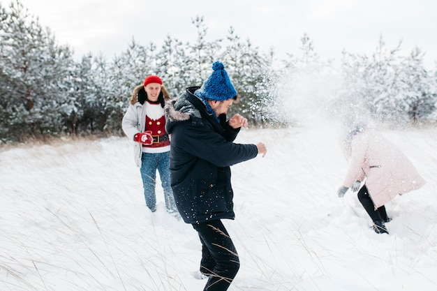 Friends playing snowballs in winter forest