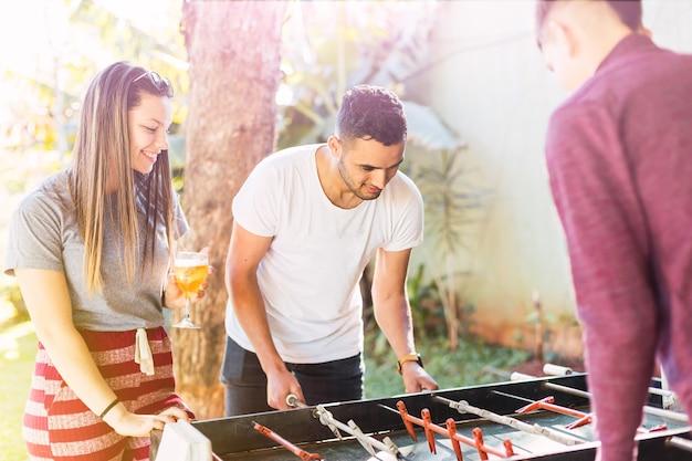 Друзья играют в настольный футбол на открытом воздухе