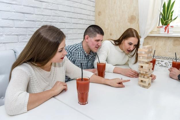 Друзья играют в башню, вынимая деревянные блоки