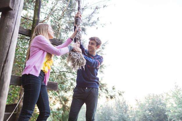 Друзья играют с веревкой в парке