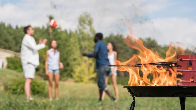 Amici che giocano con la palla accanto al barbecue