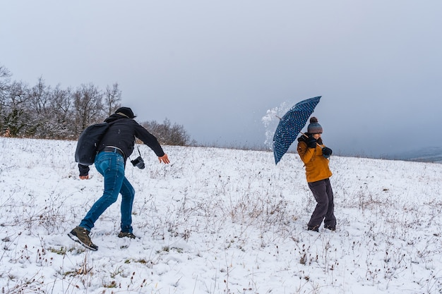 Friends playing with snowballs in the snow snow in the town of opakua near vitoria in araba
